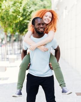 彼のガールフレンドを運ぶ彼氏の正面図