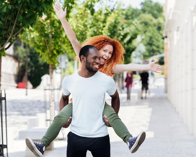 異人種間のカップルが楽しんでの正面図