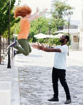 彼女の恋人の腕の中でジャンプ女性