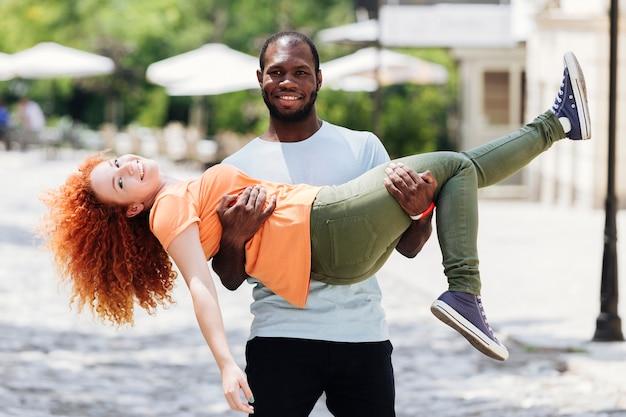 彼のガールフレンドを彼の腕の中で運ぶ彼氏