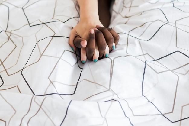 カップルがベッドで手を繋いでいます。