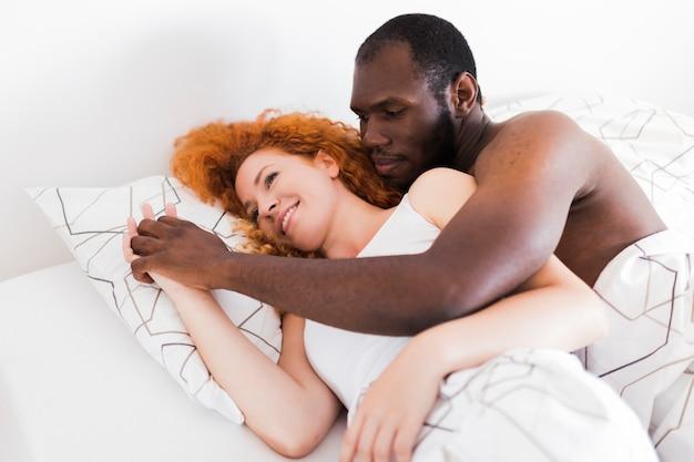 Межрасовый пара, держась за руки в постели