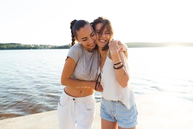 Средний выстрел женщины обнимаются рядом с озером