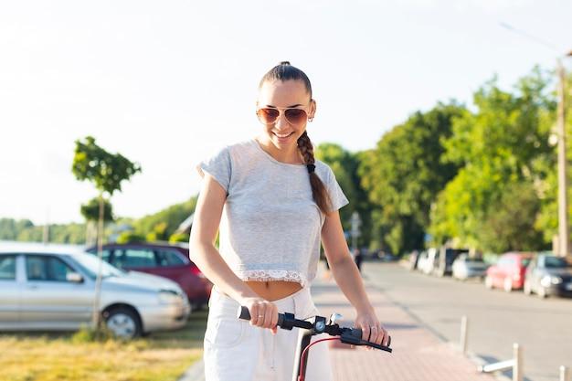 屋外のスクーターに乗って女性