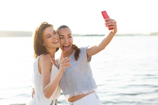 Средний снимок красивых друзей, принимающих селфи рядом с озером