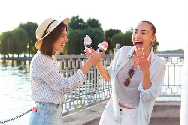 Молодые женщины, имеющие мороженое