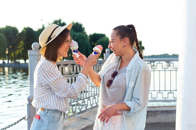 Улыбающиеся женщины играют с мороженым
