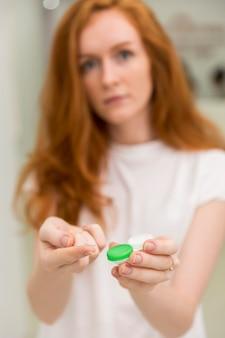 Затуманенное женщина показывает контактные линзы с его контейнером