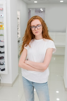 腕を組んで立っている光学ショールームで魅力的な若い女性の肖像画