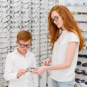 光学店で彼女の兄弟に光景を与える若い女性の肖像画