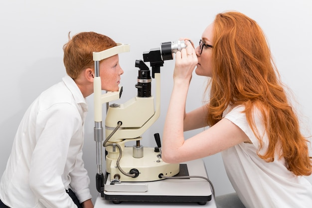 Женский глазной врач проверяя глаза мальчика с машиной рефрактометра в клинике