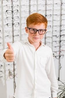 Молодой мальчик с зрелищем показывая большой палец руки вверх в магазине оптики