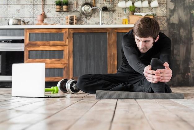 Спортсмен растягивается на тренировочном мате