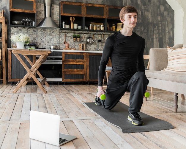 Сосредоточенный человек делает упражнения с гантелями