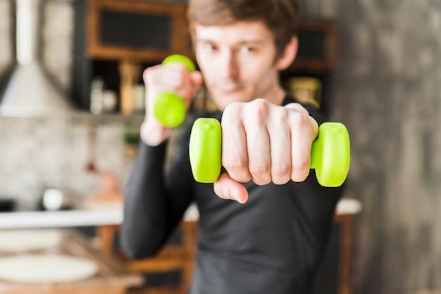 Сосредоточенная тренировка спортсмена с маленькими гантелями