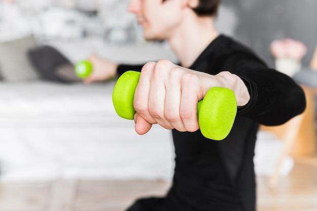 男のトレーニングと緑色のダンベルを持ち上げる
