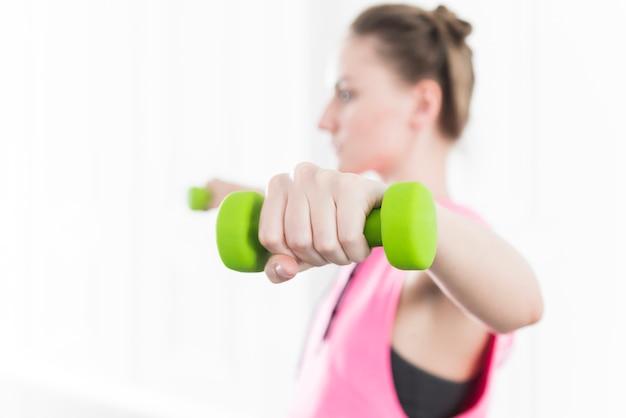 Леди тренируется и поднимает зеленые гантели