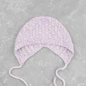スレートの背景にかぎ針編みの紫の帽子