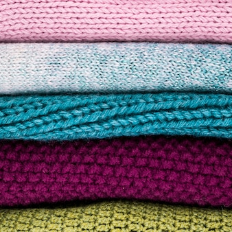 かぎ針編みのカラフルなウールの服を積み上げ