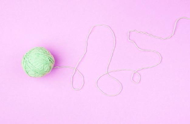 ピンクの背景に緑の糸玉