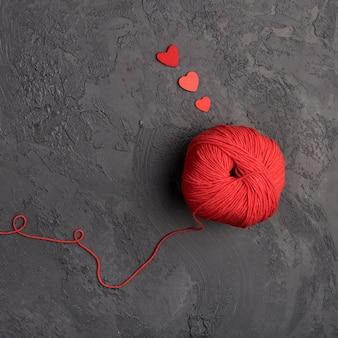 スレートの背景に赤い羊毛ボール