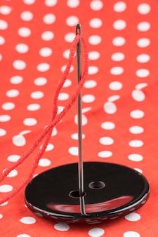 パターンの背景を持つ黒いボタンの針