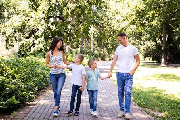 Семья из четырех человек гуляет в парке