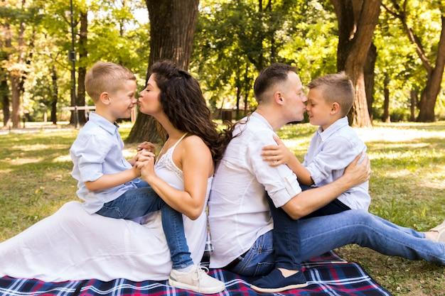 Родители целуют своих детей