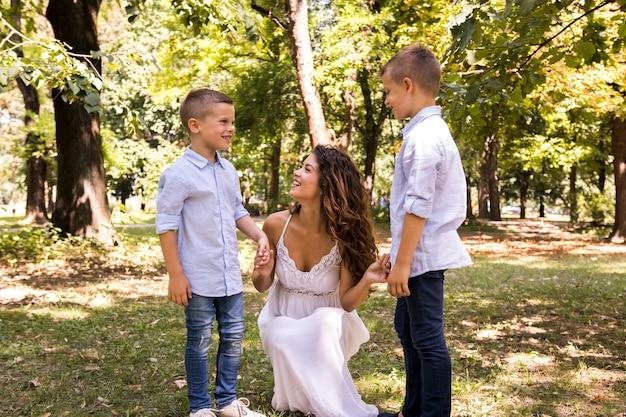 Вид спереди матери с сыновьями, проводить время в парке