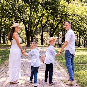 Вид сзади прекрасной семьи смотрит в камеру