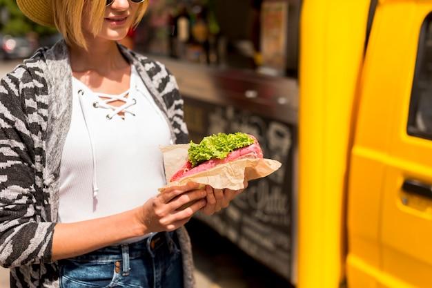 サンドイッチを保持しているクローズアップの女性