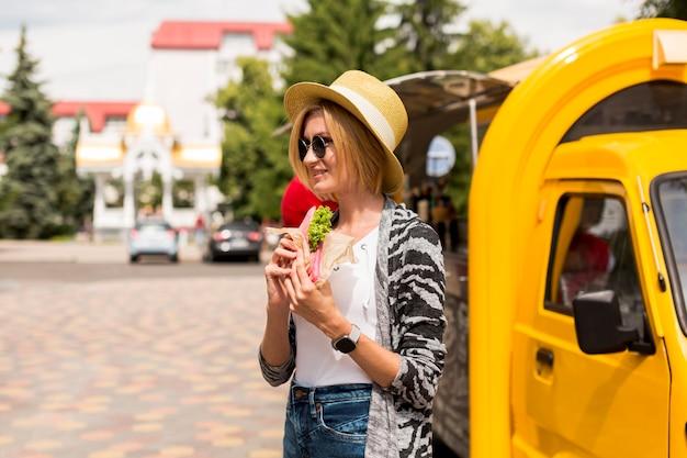 Женщина ест бутерброд и смотрит в сторону