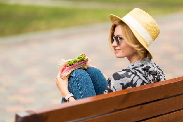 サンドイッチを押しながらよそ見の女性