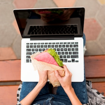 Женщина держит бутерброд перед ноутбуком