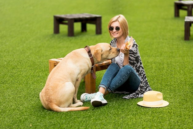 女性と犬が公園で食べ物を食べる