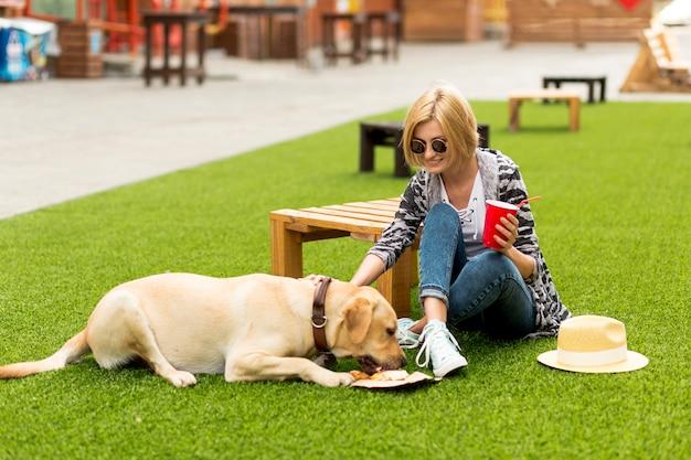 女性は公園で彼女の犬をペットにします。