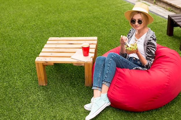 サラダを楽しんで座っている女性