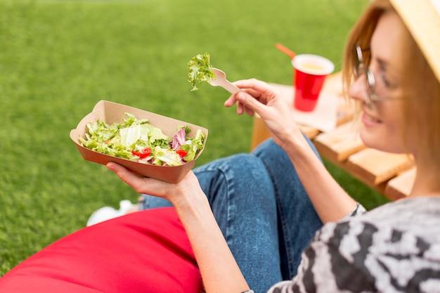 Женщина улыбается и ест в парке