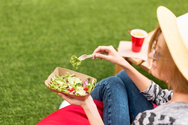 Женщина ест салат в парке