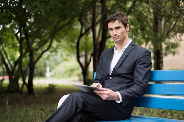 青いベンチに座っている男
