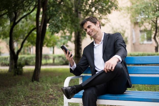 ビジネスの男性が公園で彼の携帯電話をチェック