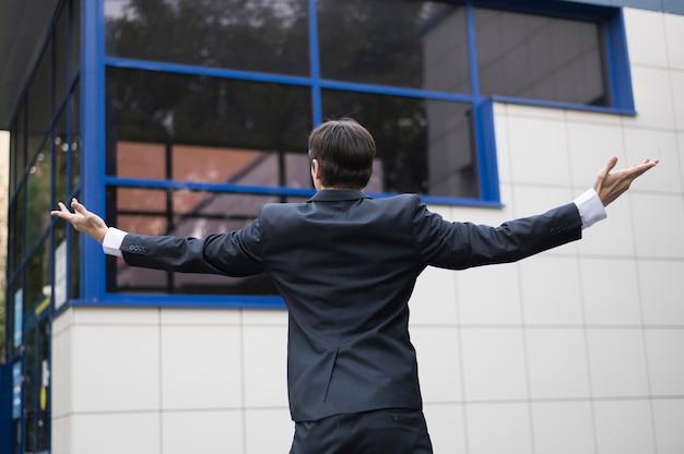 ビジネスマンおよび建物の背面図