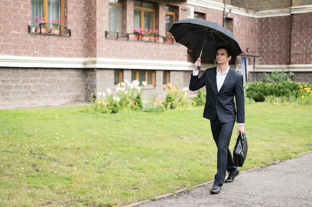 Длинный выстрел бизнесмена, держа зонтик