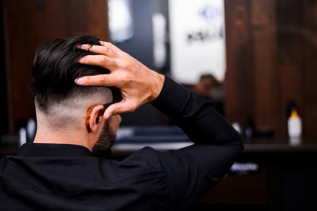 彼の髪を配置する男の背面図