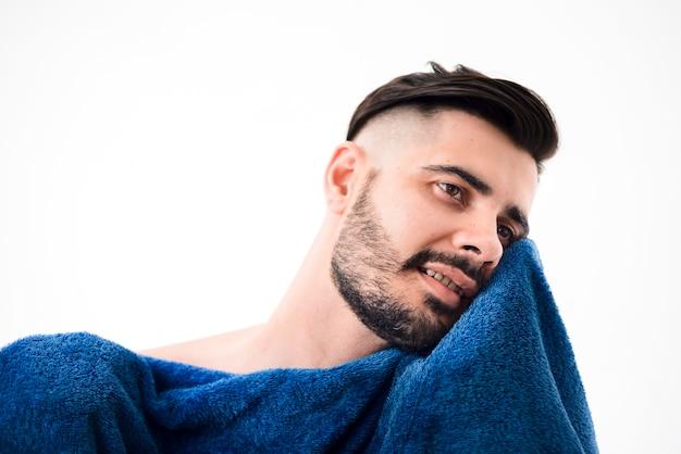 Красивый мужчина вытирает себя голубым полотенцем
