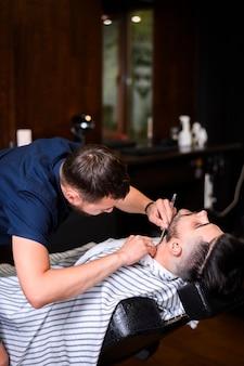 Человек получает отделку бороды в салоне