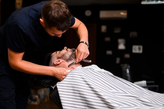 かみそりでひげを整える男