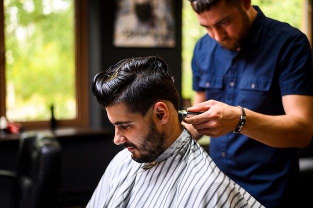 クライアントに新しい髪型を与える理髪師のミディアムショット