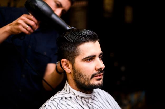 彼のクライアントの髪を乾かす理髪師