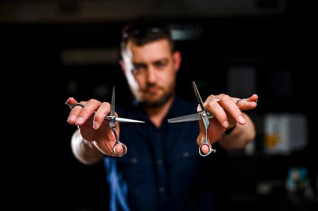 Крупный план стилиста, держащего ножницы